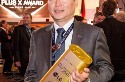LG Germany president, Young Woong Lee, holding up the Most Innovative Brand of the Year award at the Plus X Awards ceremony
