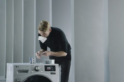 A professional card stacker Bryan Berg building house of card atop an LG Centum System™ washing machine
