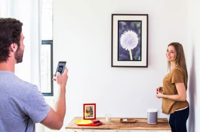 A man uses art streaming platform, Acanvas, to connect his phone to one of its cord-free customizable digital frames, while a woman oversees with a smile on her face