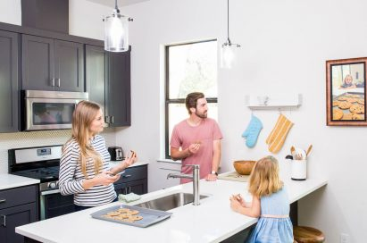 A family of three observe personal photos on their new digital frame by Acanvas in their kitchen.