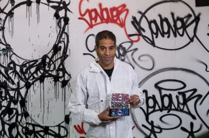Popular artist JonOne holding up exclusive devices from the LG Portable Speaker art series