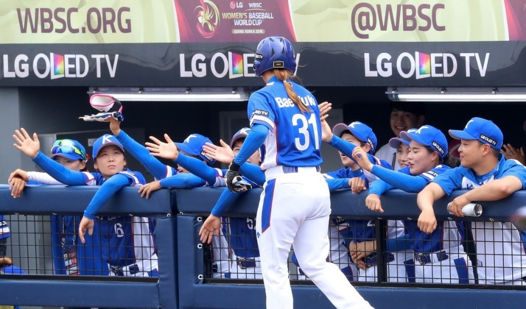 South Korean player hi-fives teammates in dugout with LG OLED TV logo in background