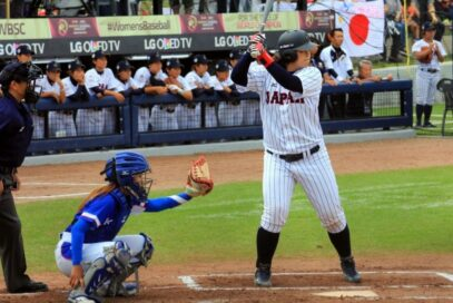 Japan player awaits pitch from South Korean rival with OLED TV logo visible above Japan's dugout