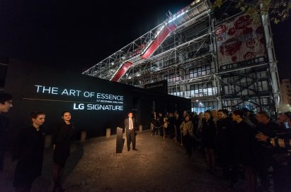 An LG official stands before sign with 'The Art of Essence' LG SIGNATURE brand message at opening of LG SIGNATURE Gallery