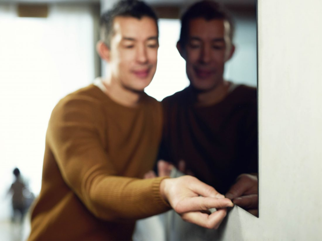 A man tries to tug on the screen of an LG SIGNATURE OLED TV W which hangs flush against the wall.