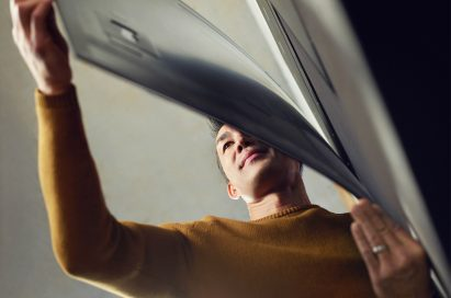 A man tugs on the bottom of the screen of LG SIGNATURE OLED TV W and admires the slender form of it.