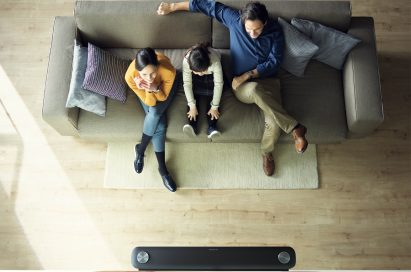 Another view of a family sitting in their living room looking at the LG SIGNATURE OLED TV W (model W7) which is mounted on the wall