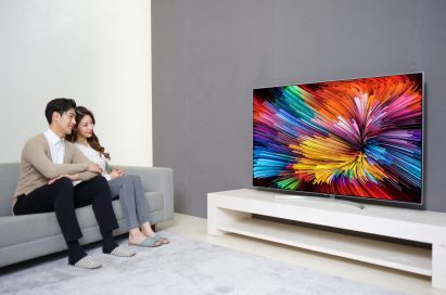 A different shot of a couple sitting on a couch watching the LG SUPER UHD TV (model SJ95)
