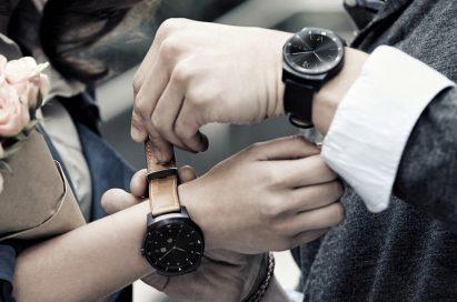Man wearing an LG G Watch R with black strap helps to put a G Watch R with tan strap on woman's wrist