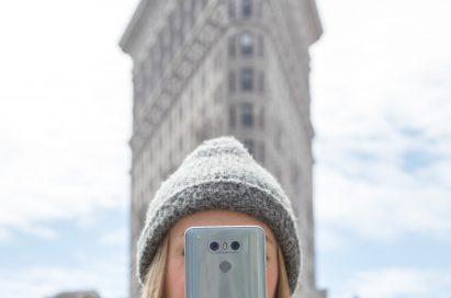 A woman holds the LG G6 in Ice Platinum up in front of her face while standing in front of the Flatiron Building in New York, USA