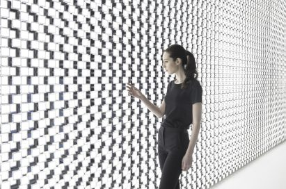 A wider angle of a woman touching one of the thousands of bright lights found on the back wall of Tokujin Yoshioka's art exhibition.