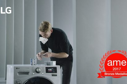 A professional card stacker Bryan Berg building house of card atop an LG Centum System™ washing machine with AME Award 2017 logo featured