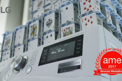 Closeup of LG Centum System™ washing machine and house of card built on it with AME Award 2017 logo featured