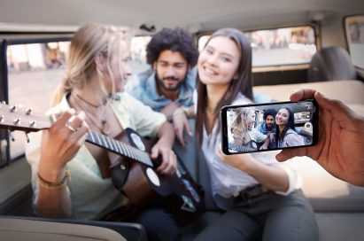 A person taking a picture with the LG Q6 of band member inside a van