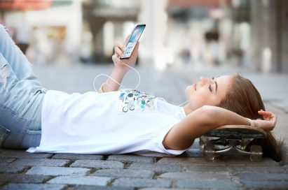 A woman is lying down listening to music with the LG Q6 in Ice Platinum via headphones