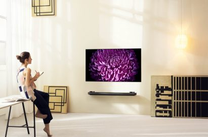 A woman sits mesmerized by an LG SIGNATURE OLED TV displaying the image of a beautiful flower