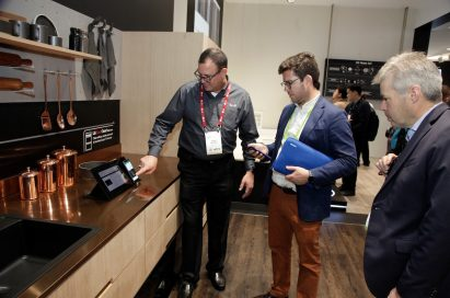 A gentleman demonstrates the enhanced connectivity of LG's ThinQ AI-powered home appliances to visitors of CES 2018.