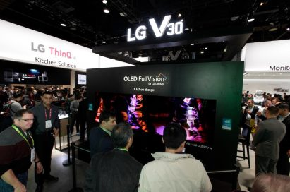 LG staff members speak with visitors in front of the LG V30's CES display which boasts LG's OLED FullVision TVs too