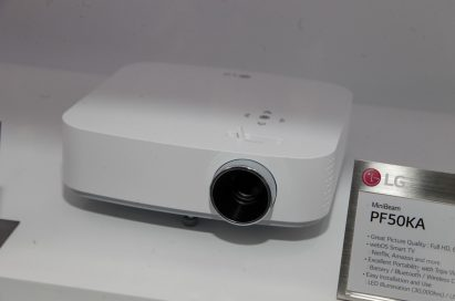 Upper front view of LG's MiniBeam PF50KA projector placed next to its nameplate
