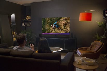 A man and woman seated on a couch in their living room at night watching a couple laying in long grass on their LG AI OLED TV