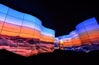 A wide-angled shot of the LG OLED Canyon displaying imagery of a sunrise above the clouds at CES 2018