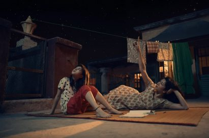 """A screenshot of LG India's """"Astronaut"""" video, there are two women looking up towards the night sky"""
