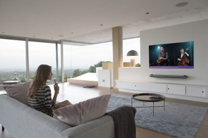 A model speaking directly into the remote control via LG ThinQ and turning on her favorite Jazz hits