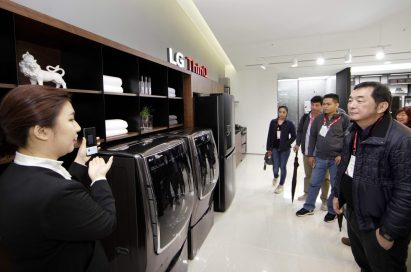 A female presenter introduces LG ThinQ AI features that can control LG's home appliances by using LG's smartphones.