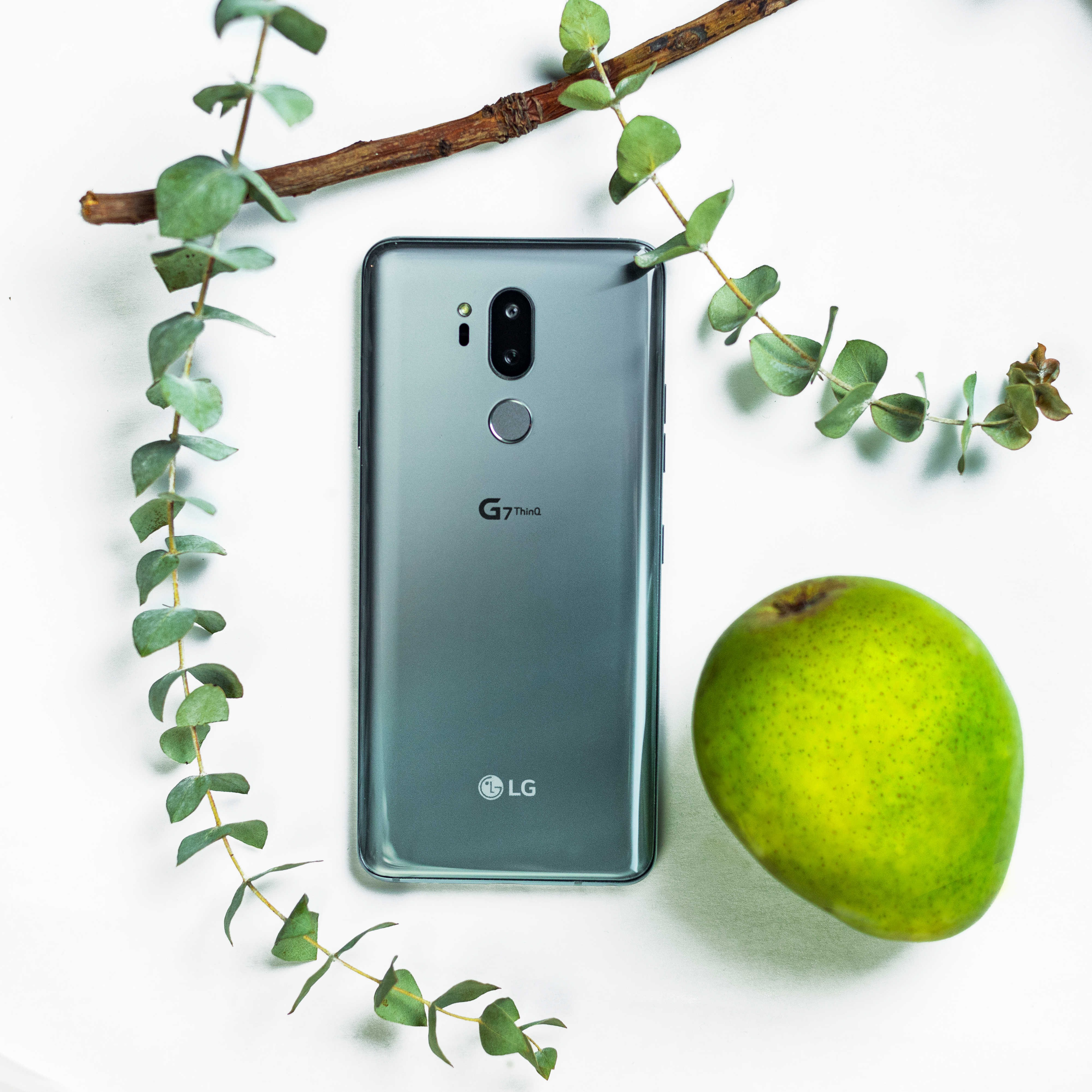 The LG G7 ThinQ in New Platinum Gray face down next to a green pear