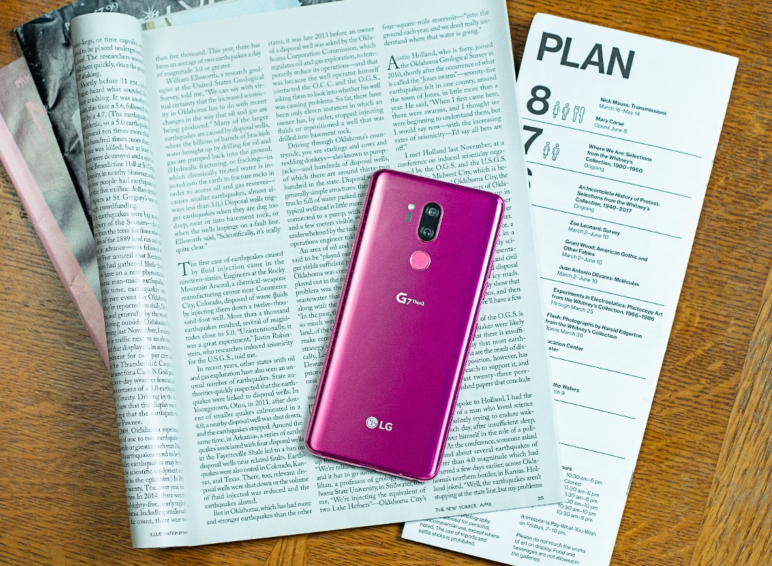 The LG G7 ThinQ in Raspberry Rose face down on top of an open magazine