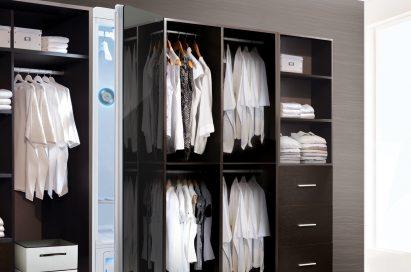 LG Styler with door slightly open inside a walk-in closet