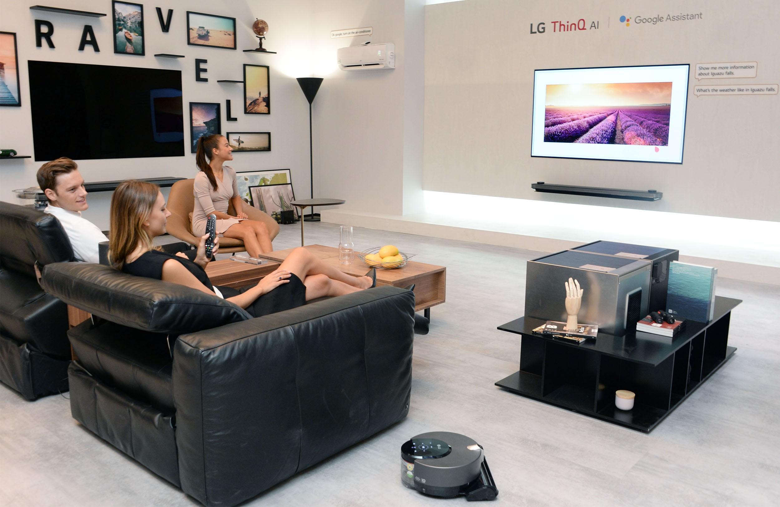 Models pose with LG ThinQ AI TV at the LG booth at IFA 2018.