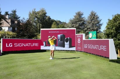 A golfer hits a ball right in front of the LG Signature signage.