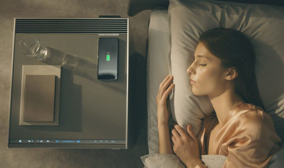 A woman sleeps with an LG OBJET Air Purifier next to her bed; a glass of water, smartphone and books have been placed on top of the purifier