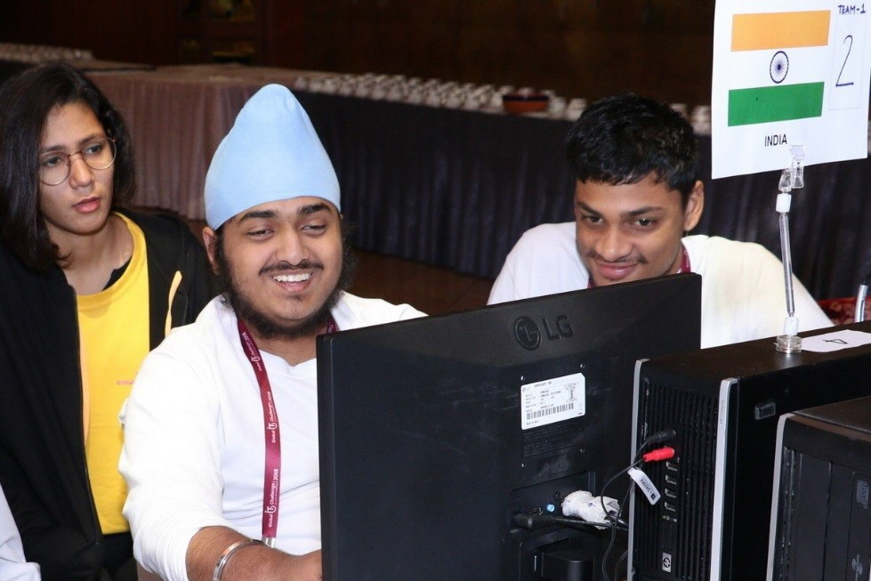 Members of the India team smile while looking at the LG monitor