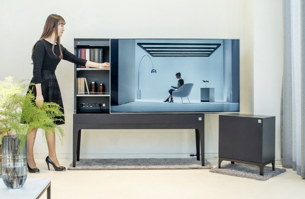A woman slides open the display panel of LG Objet TV in order to use the storage hidden behind the panel