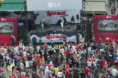 A big crowd dance to the upbeat TWINWash song in front of stage at LG's TWINWash Song & Dance campaign