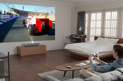 A man playing a video game with the LG CineBeam Laser 4K projector model HU85L