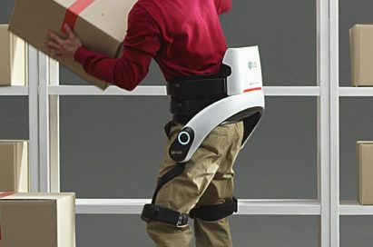A man lifts a heavy box onto a high shelf while wearing LG CLOi SuitBot