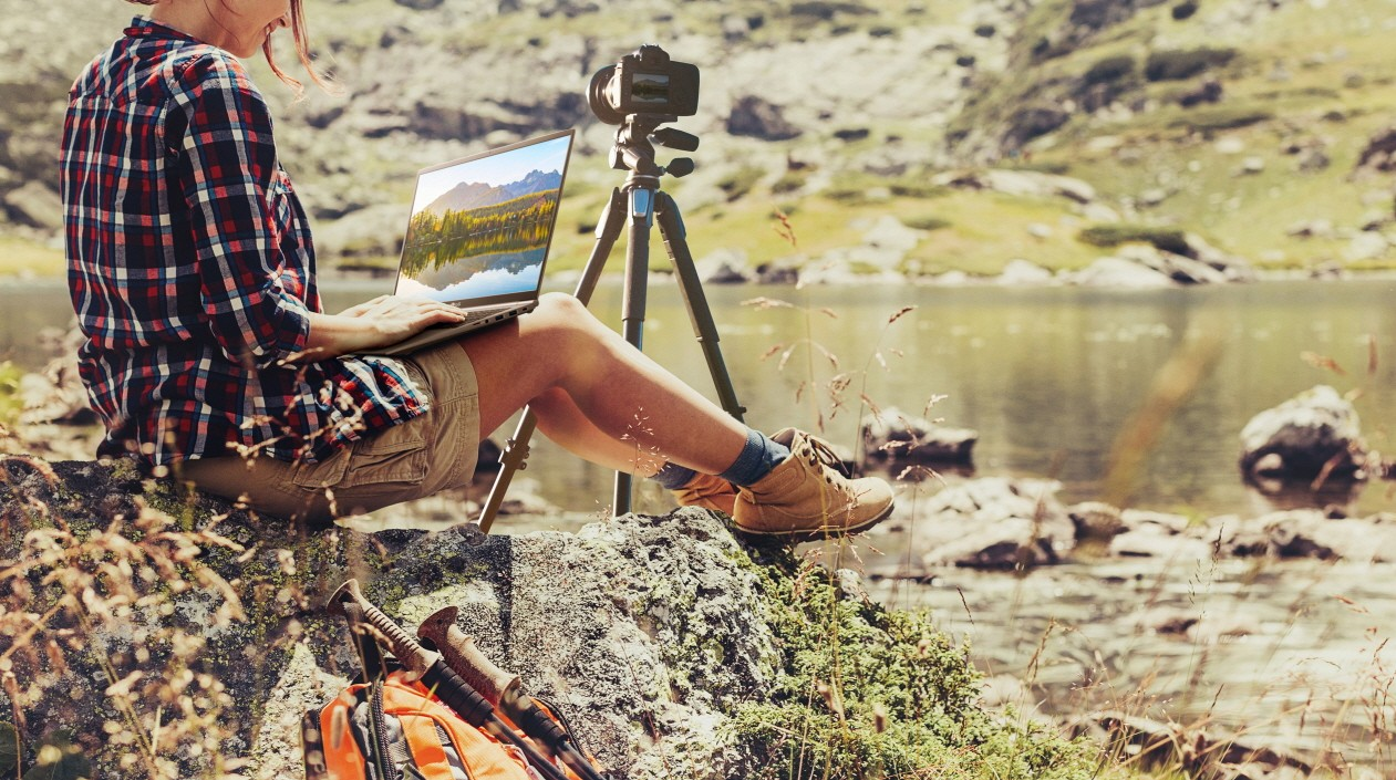 A lady working on pictures with her LG gram while sitting on a rock beside the river