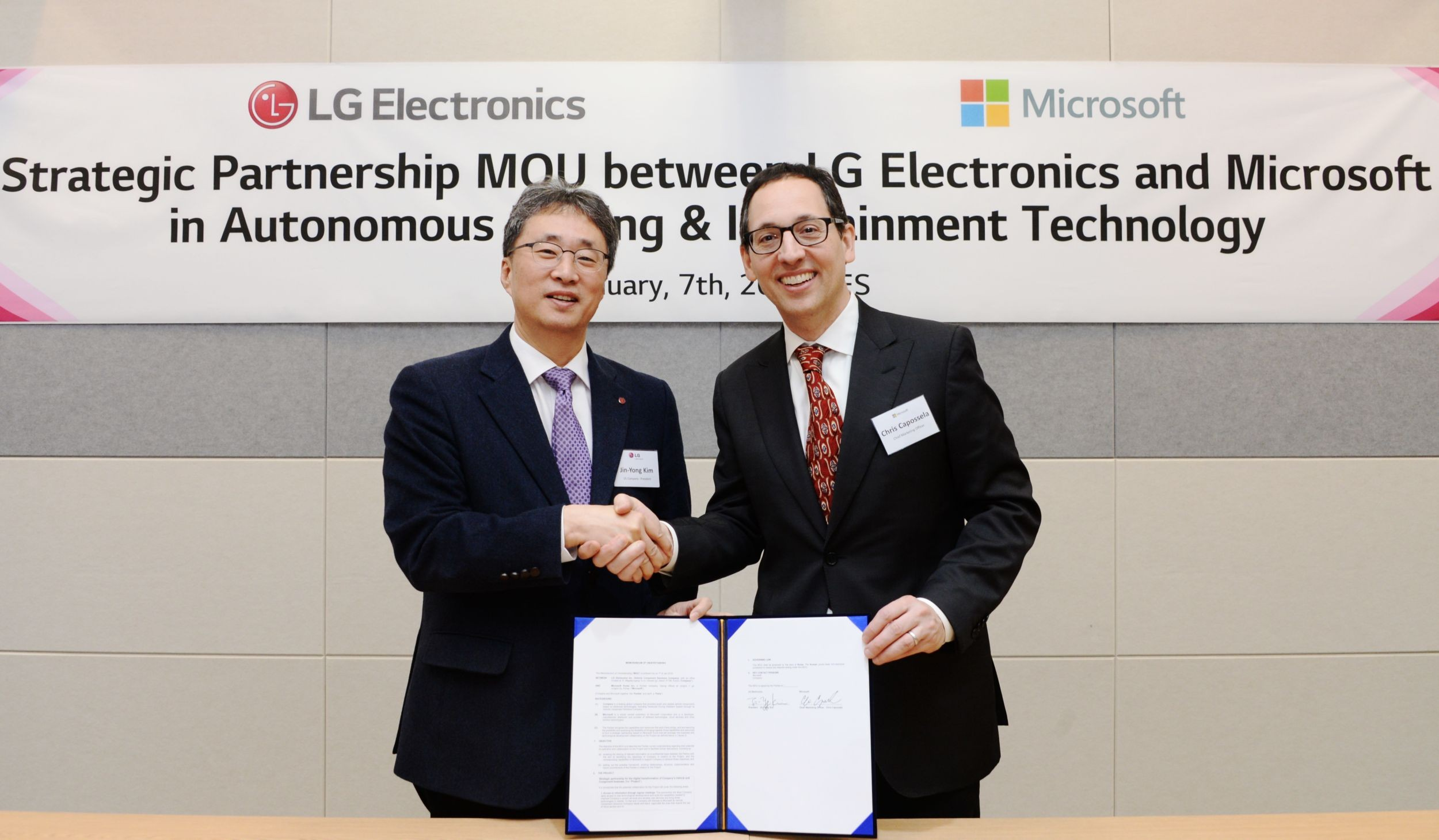 Mr. Kim Jin-yong, president of LG's Vehicle Component Solutions Company, shake hands with Mr. Sanjay Ravi, general manager, automotive industry at Microsoft.