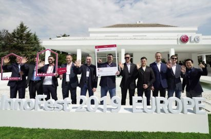 Attendees of LG InnoFest 2019 Europe wave their hands towards the camera in front of LG Home Madrid.