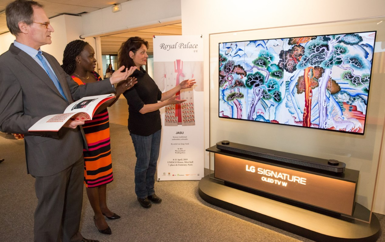 """Three visitors look at the LG SIGNATURE OLED TV W which displays a """"chasu"""" artwork."""