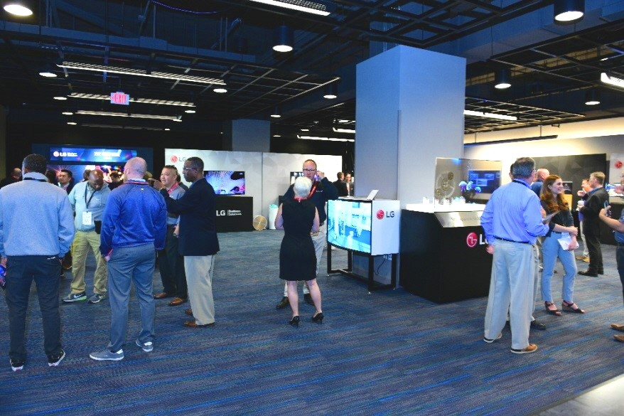 A looking inside the 2019 LG TechTour's venue, with attendees browsing and discussing LG's B2B products