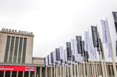 """Partial view of Messegelände Berlin ExpoCenter City with promotional flags of the LG SIGNATURE brand and its brand theme """"The Art of Essence"""" flying in front"""
