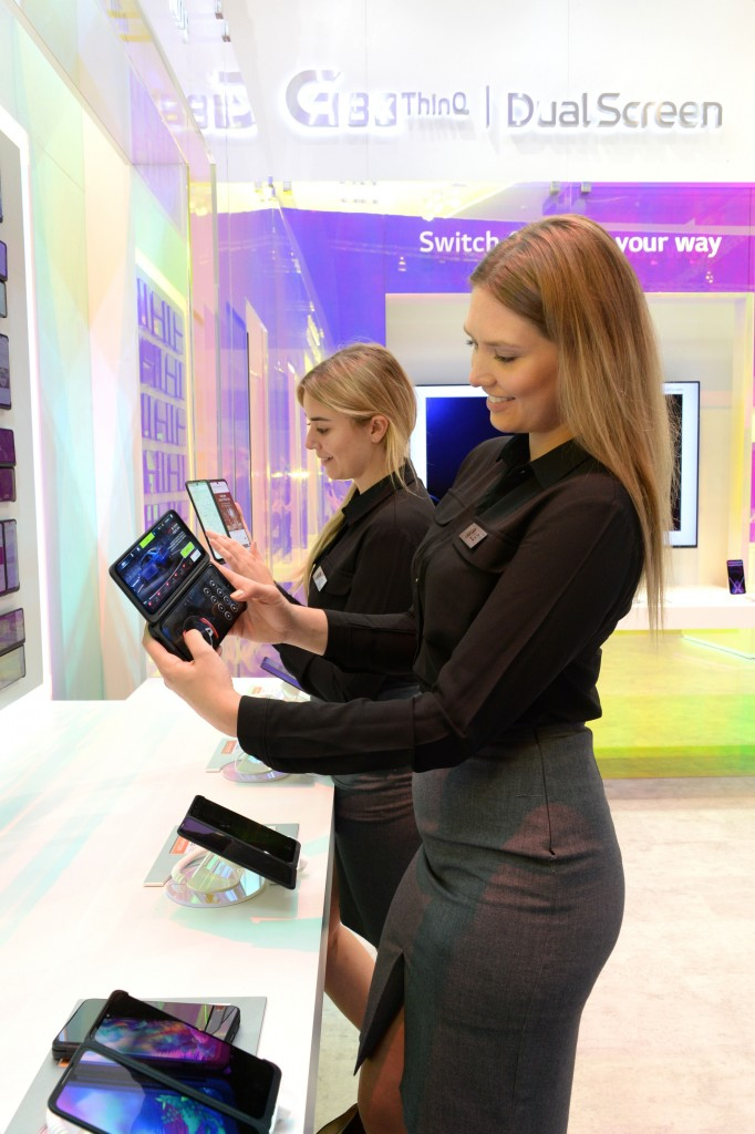 Two female models look at LG G8X ThinQ with the Dual Screen feature in front of some samples of the LG G8X ThinQ phones.