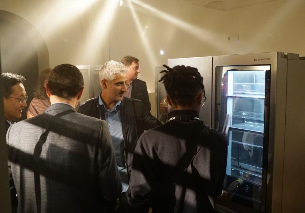 Attendees discuss the LG InstaView Door-in-Door refrigerator at LG SIGNATURE's exhibition space.