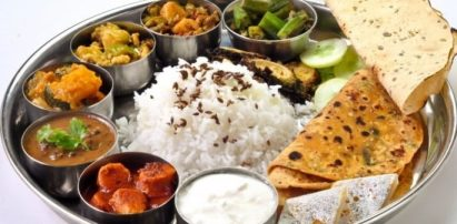A round metal dish full of Indian food