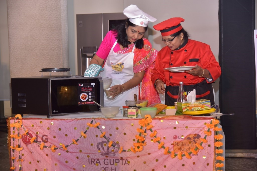 Two event's participants cook their Indian food by using LG's microwave ovens at the LG Mallika-E-Kitchen contest.