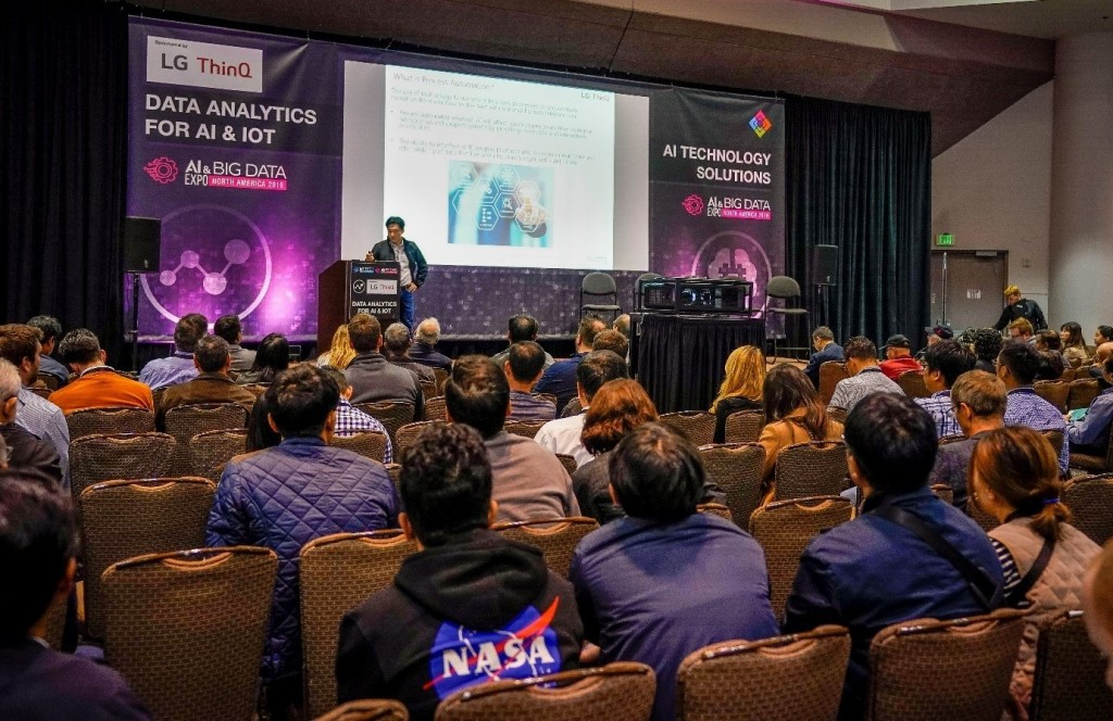 Samuel Chang, corporate vice president of the LG Silicon Valley Lab, discusses Process Automation from IoT Data in front of a large audience, with a large banner bearing the LG ThinQ logo behind him.